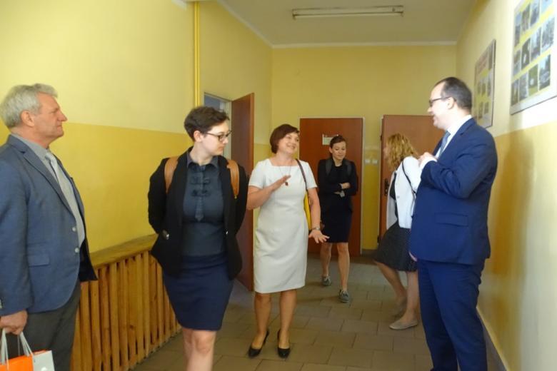 Cztery osoby na korytarzu. Kobieta w białej sukeince rozmawia z mężczyzną w garniturze