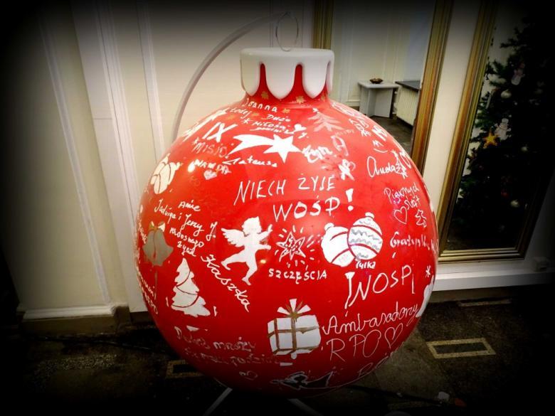 na zdjęciu: duża czerwona bombka ozdobiona białymi napisami i rysunkami