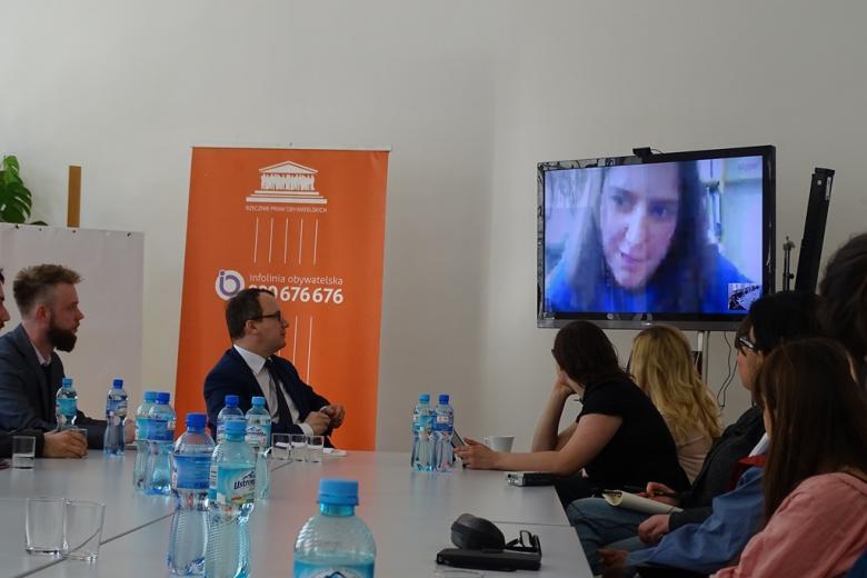 Zdjęcie: zebrani słuchają wystąpienia uczestniczki, którą widać na dużym telwizorze
