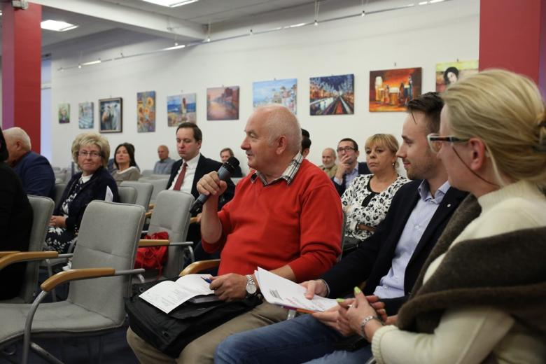 Mężczyzna w czerwonym swetrze mówi do mikrofonu