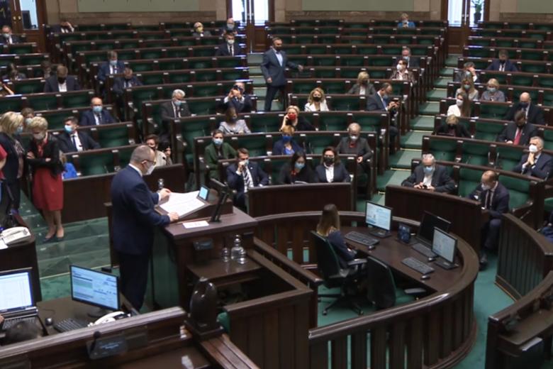 mężczyzna na mównicy w Sejmie, w tle parlamentarzyści