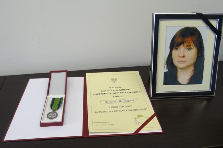 Zdjęcie dyplomu i fotografii młodej kobiety z żałobną obwódką