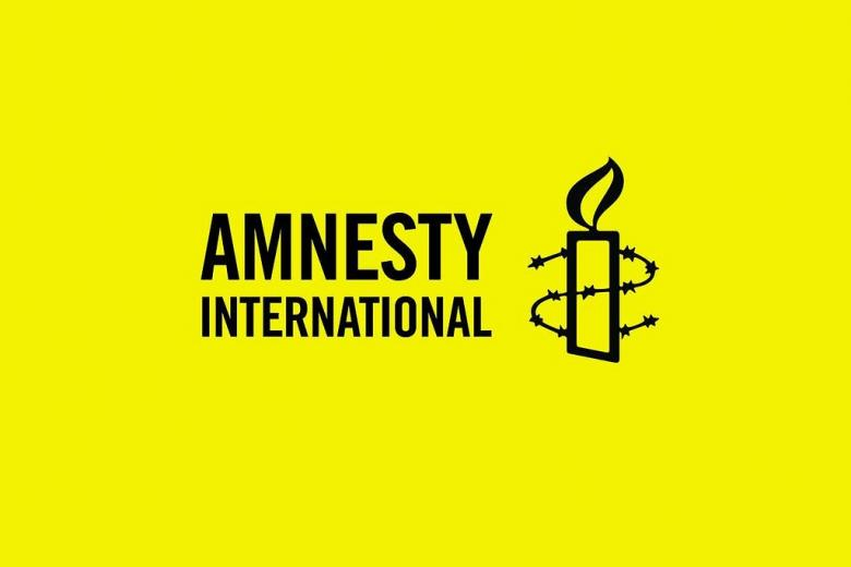 Logo Amnesty International na żółtym tle