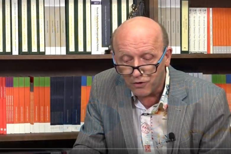 Mężczyzna czyta bajkę na tle półek z książkami