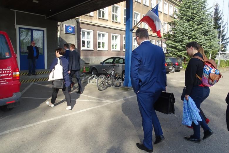 Grupa ludzi wchodzi do budynku szkoły z panstwową i unijną flagą