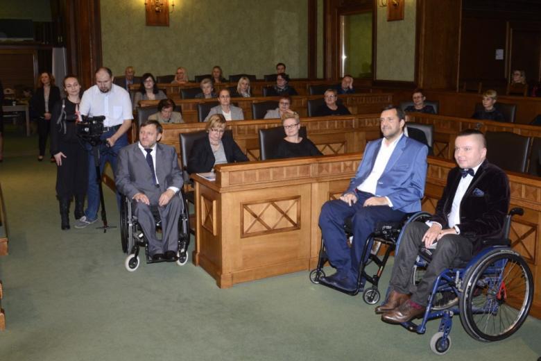 Dwaj mężczyźni na wózkach, ludzie na sali