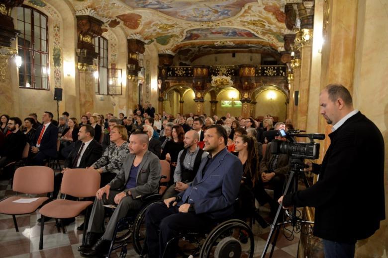 Ludzie w zabytkowej sali, dwaj mężczyźni na wózkach