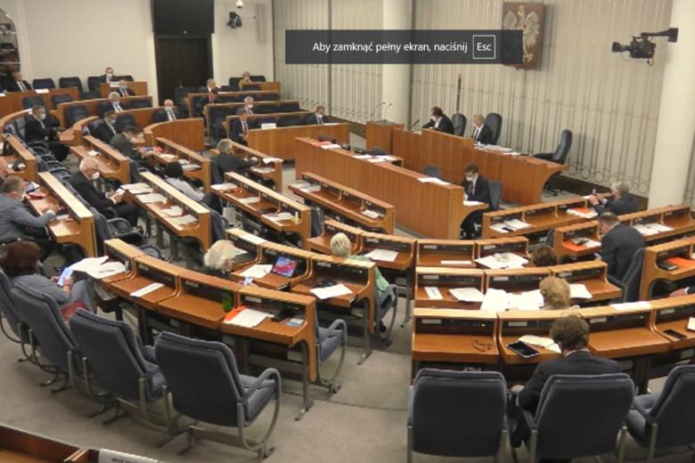 osoby siedzą w sali Senatu