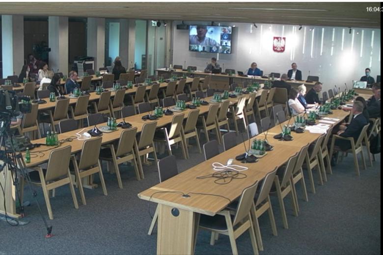 Osoby siedzą w sali