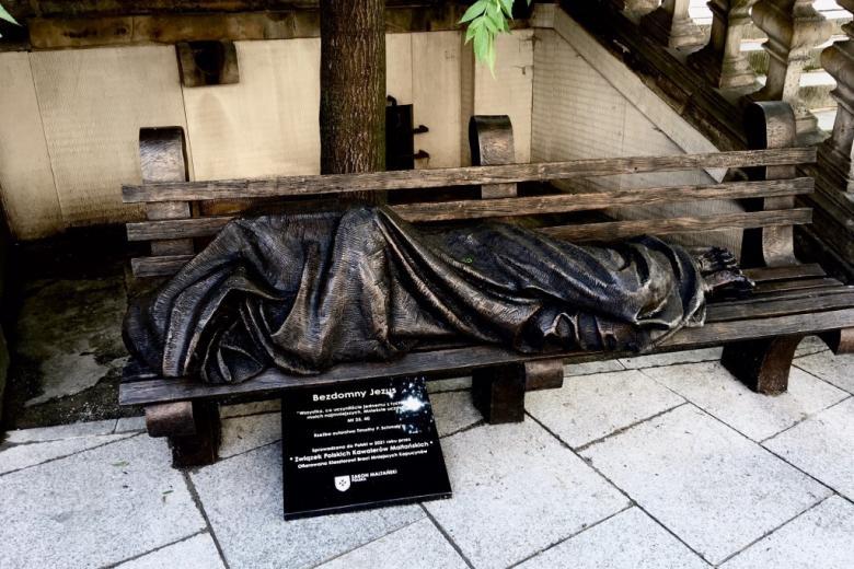 Pomnik przedstawiający postać śpiącą na ławce