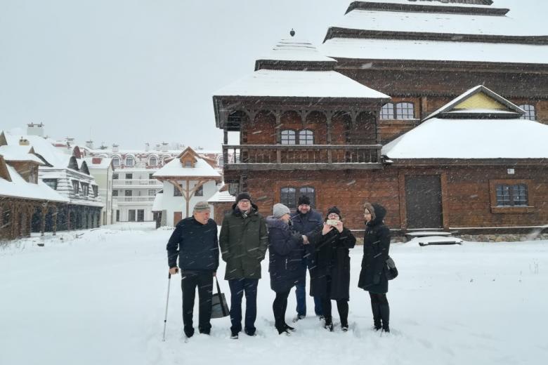 Zdjęcie grupowe w śniegu na tle drewnianych domów