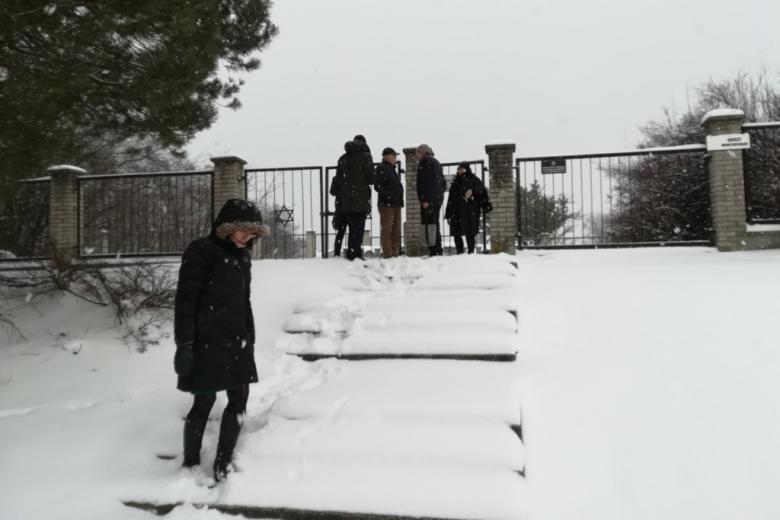 Grupa ludzi na wzgurzu otoczonym płotem