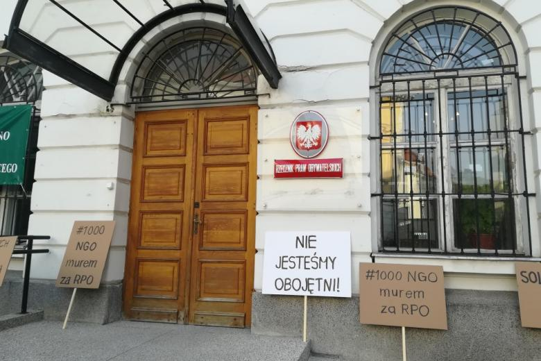 """Transparent z napisem """"Nie jesteśmy obojętni"""" pod tablicą na ścianie """"Rzecznik Praw Obywatelskich"""""""