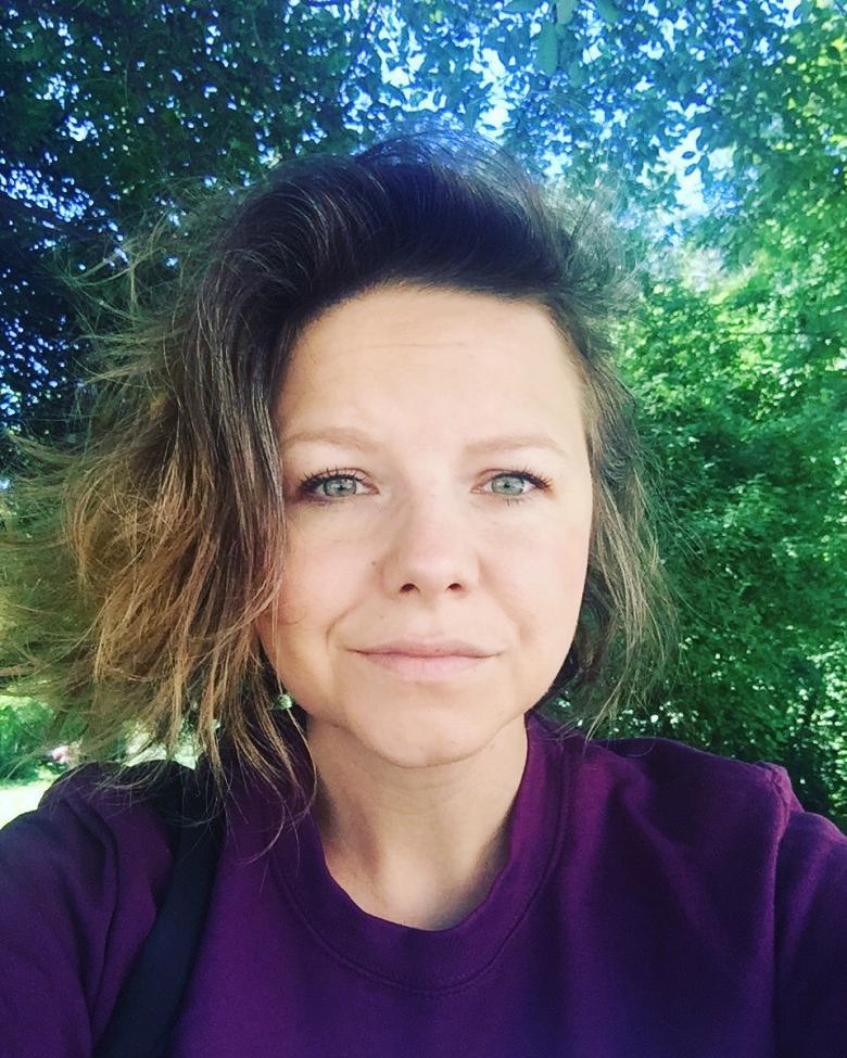 Kobieta w fioletowym stroju na tle drzew