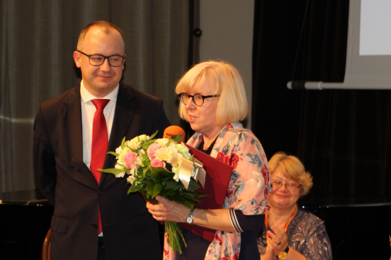 Kobieta z kwiatami i dyplomem oraz mężczyzna