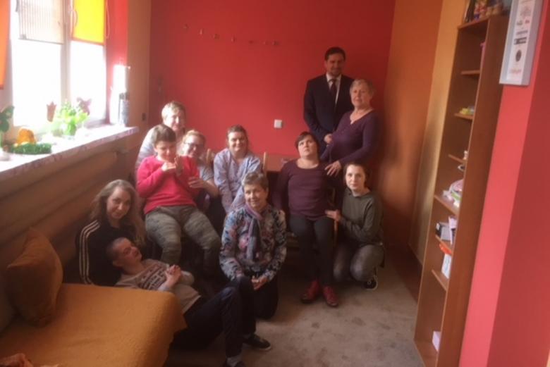 Zdjęcie grupowe, dorosle osoby z niepelnospawnościami, ich rodzice i męzczyzna w garniturze