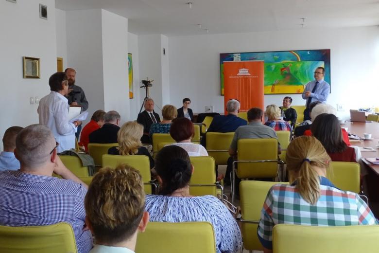Ludzie na sali, żółte krzesła, mężczyzna w koszuli