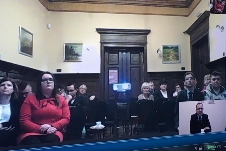 Ekran komunikatora Skype: ludzie na sali w Debnie i Adam Bodnar