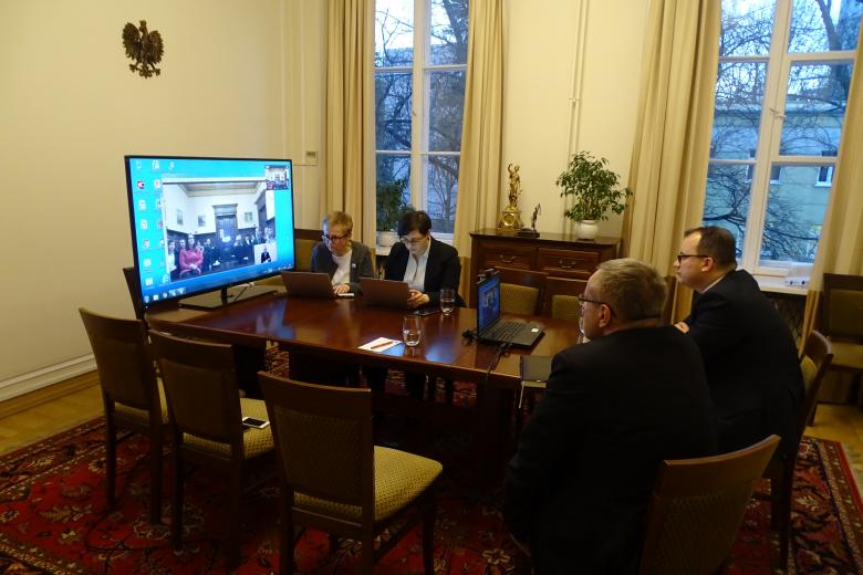 Ludzie w pokoju w urzędzie, na stole - duży monitor komputerowy, a na nim - transmisja z Dębna