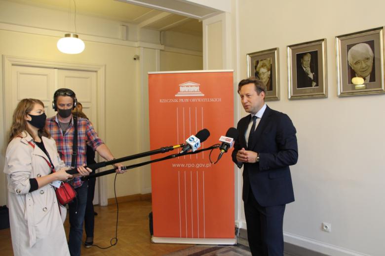 Osoba przemawia na stojąco do dziennikarzy