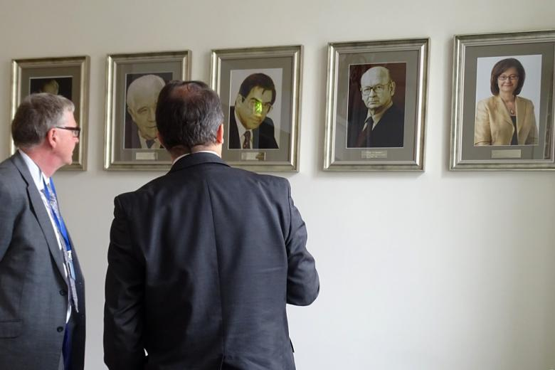 zdjęcie: dwaj mężczyźni stoją tyłem do obiektywu i odladają wiszące przed nimi na ścianie portrety