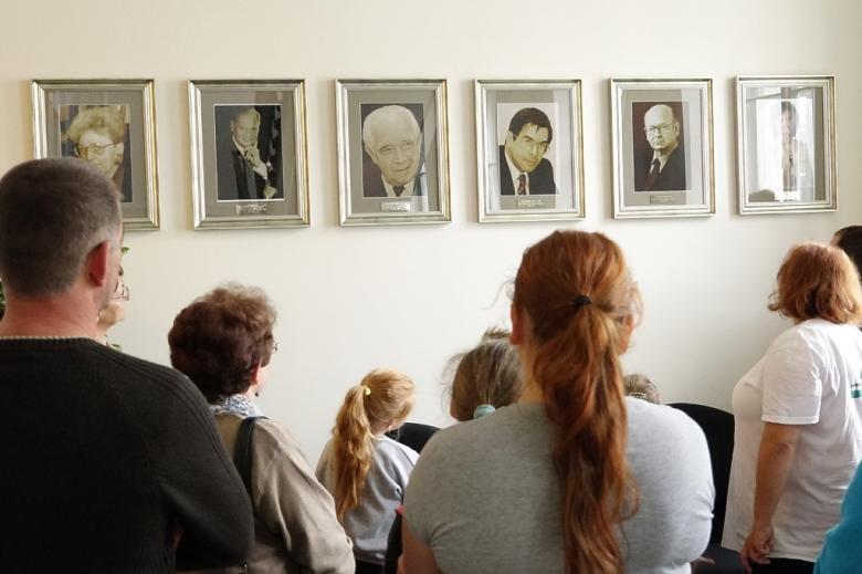 zdjęcie: kilka osoób stoi tyłem przed nimi na ścianie wili kilka portretów