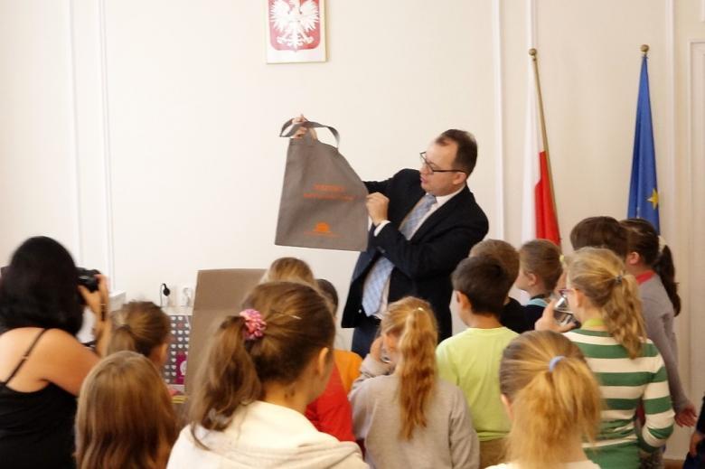 zdjęcie: mężczyzna trzyma w rękach materiałową torbę, którą pokazuje otaczającym go dzieciom