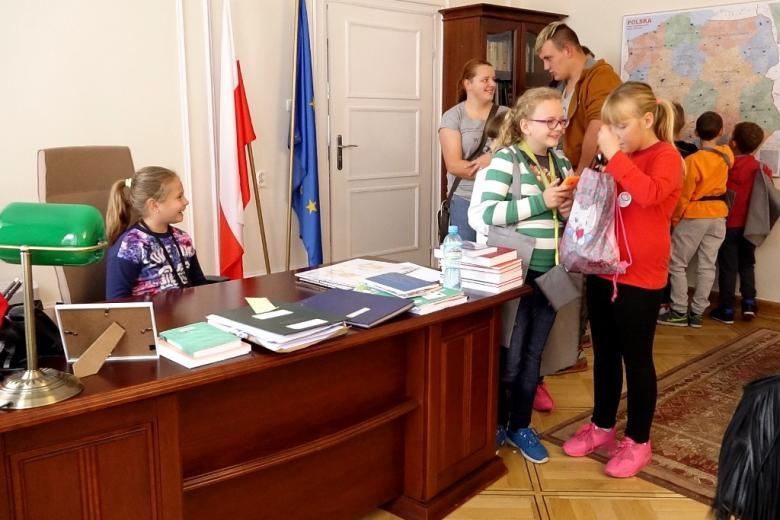 zdjęcie: po lewej stronie widać drewniane biurko, za którym siedzi dziewczynka, obok niej stoi kilkorodzieci