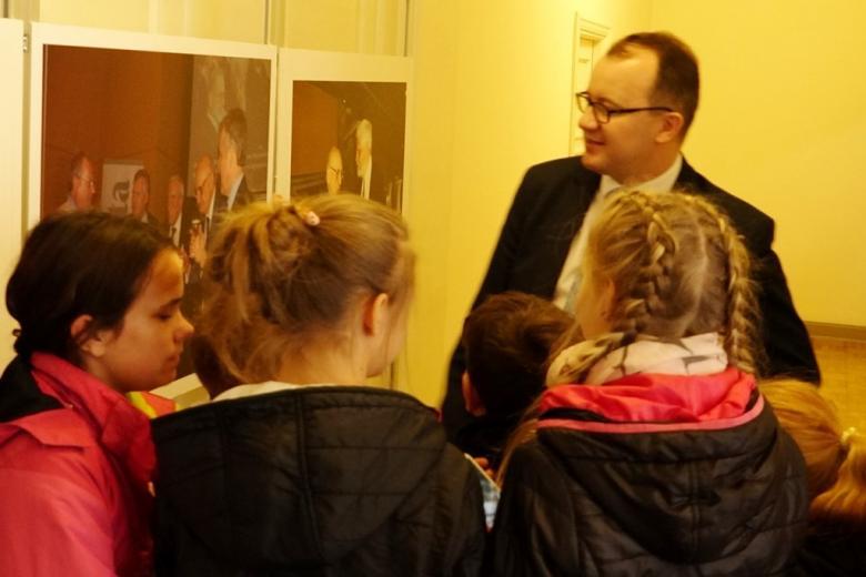 zdjęcie: tyłem stoi trójka dziewczynek, przed nimi jest mężczyzna, który opowiada o zdjęciach, które wiszą po lewej stronie