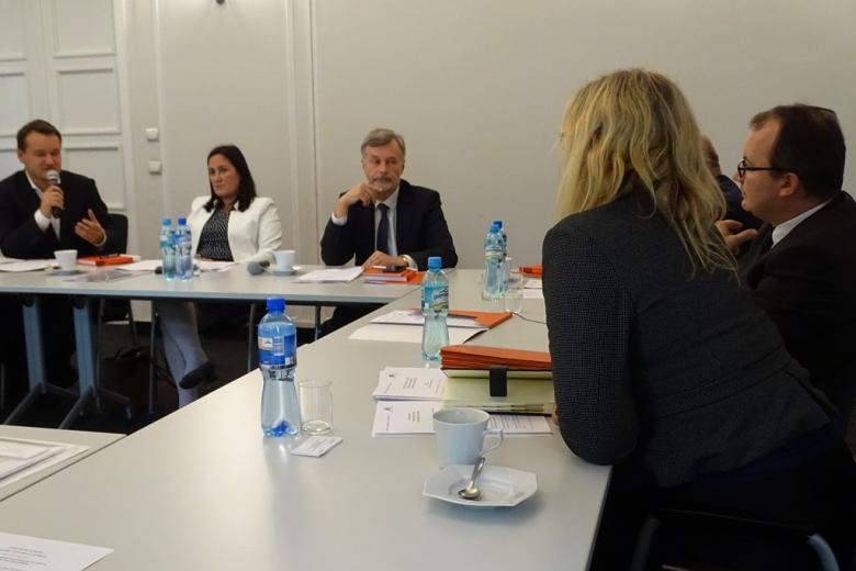 zdjęcie: kilka osób siebi przy stołach, mężczyzna mówi do mikrofonu