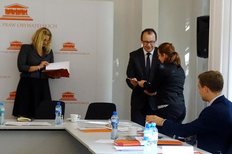 zdjęcie: kobieta i męzczyzna stoją, mężczyzna wręcza kobiecie dokumenty