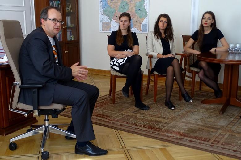 zdjęcie: mężczyzna siedzi na fotelu obrotowym, za nim widać młodych ludzi siedzących na krzesłach