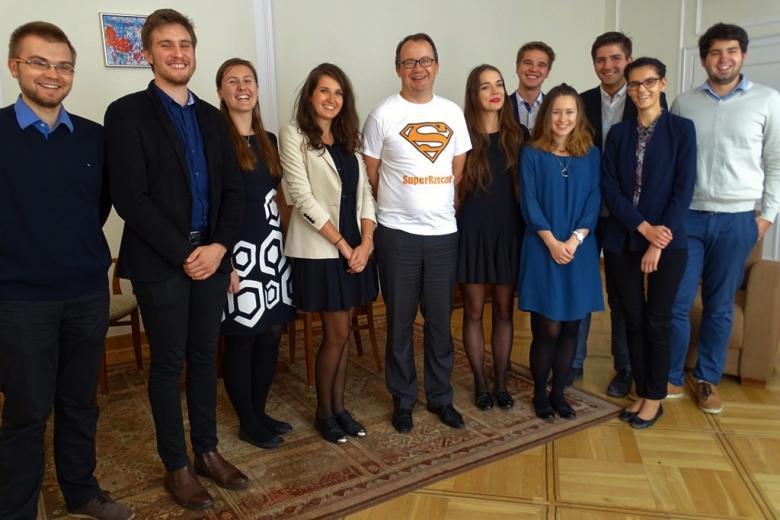 zdjęcie: grupa osób stoi, w środku jest mężczyzna w białej koszulce z logiem supermana