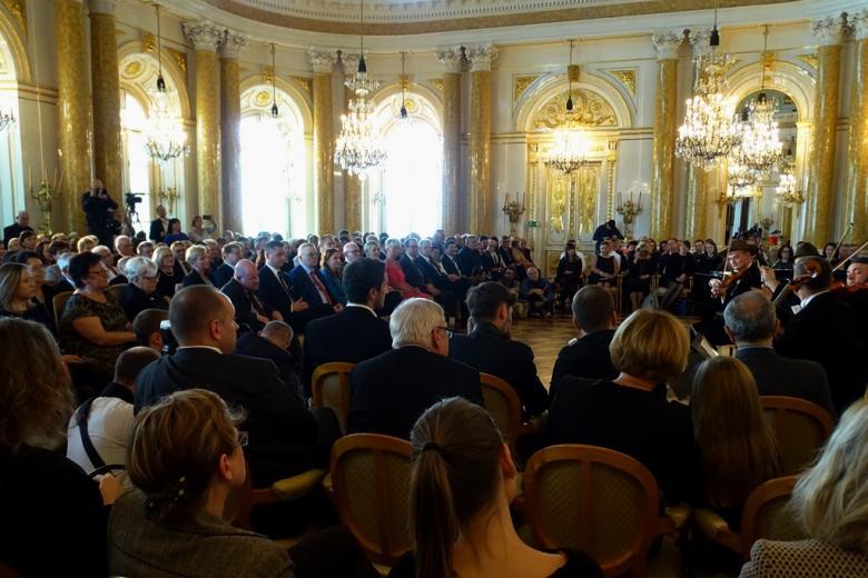 zdjęcie: kiladziesiąt osób siedzi na sali, z boku widać stojącego skrzypka