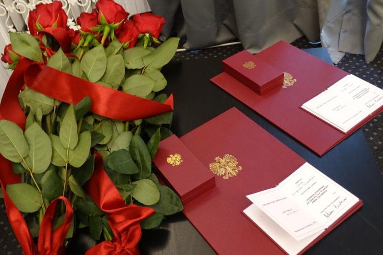 zdjęcie: na stoliku leżą bukiety czerwonych róż i burgundowe teczki z orłem