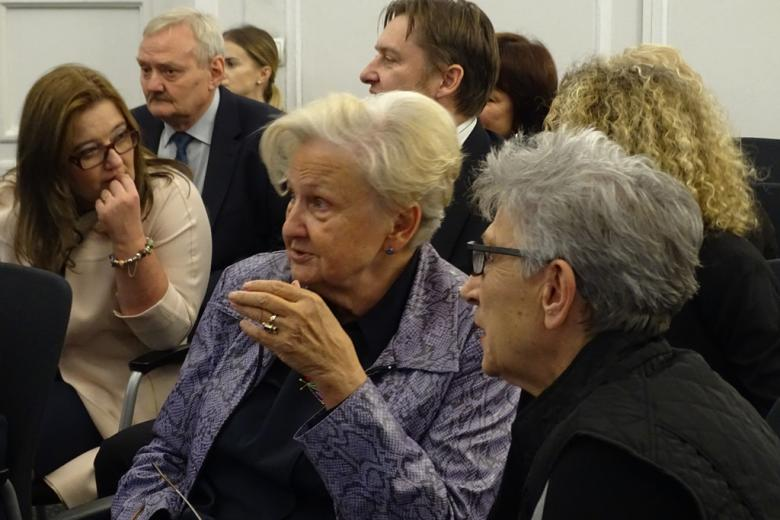 zdjęcie: kilka osób siedzi i rozmawia, na pierwszym planie dwie kobiety