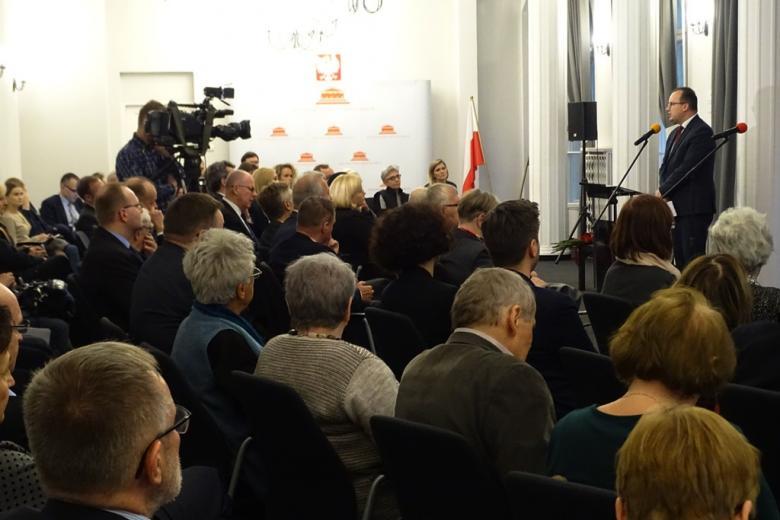 zdjęcie: na sali siedzi kilkadziesiąt osób, przed nimi stoi mężczyzna w garniturze