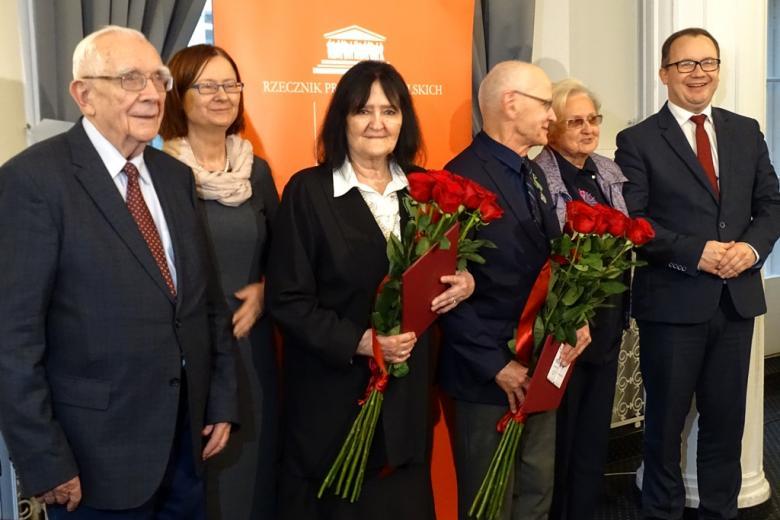 zdjęcie: trzy kobiety i trzech mężczyzn stoją obok siebie, kobieta i mężczyzna po środku trzymają bukiety czerwonych róż