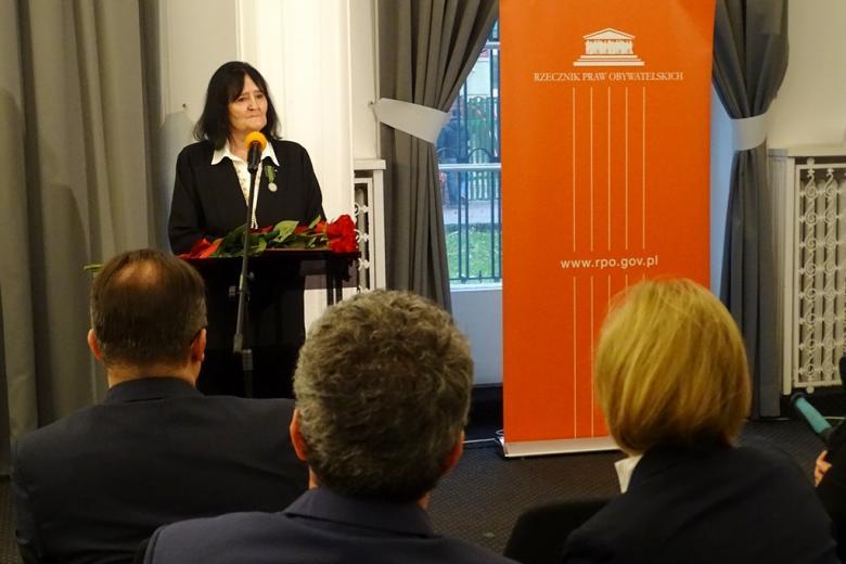zdjęcie: kobieta stoi przy mównicy, przed nią siedzi kilka osób