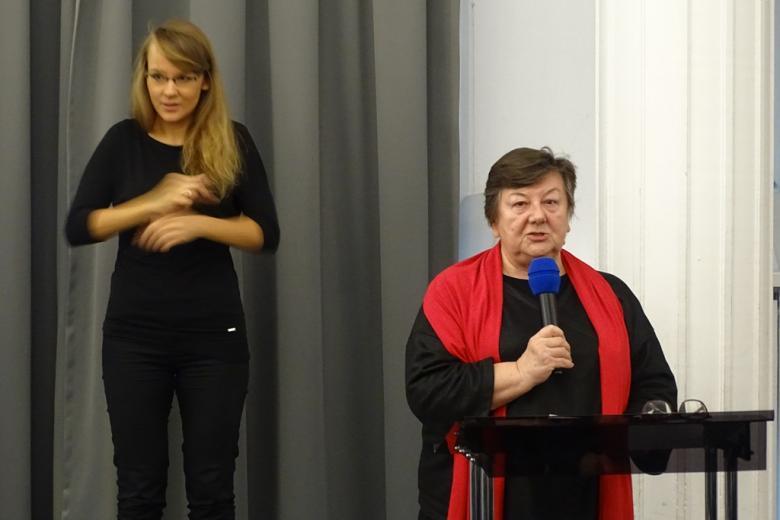 zdjęcie: kobieta w czarnej sukience i czerwonym szalu stoi przy mównicy, za nią kobieta ubrana na czarno, która gestykuluje