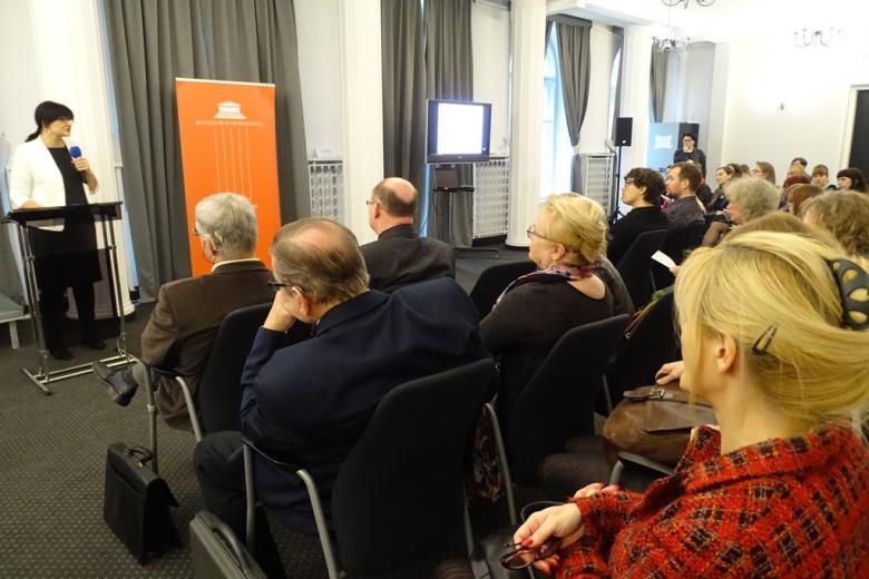zdjęcie: kilka osób siedzi na sali przed nimi przy mównicy stoi kobieta w białym żakiecie