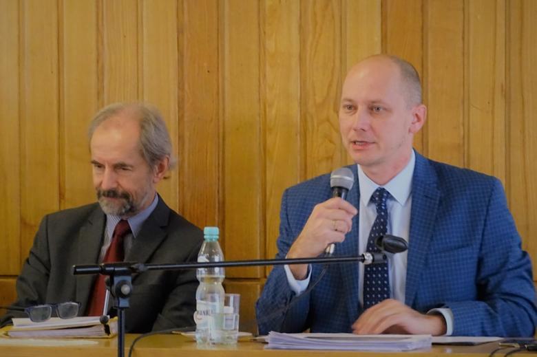 zdjęcie: dwóch mężczyzn w garniturach siedzi za stołem, jedne z nich mówi do mikrofonu