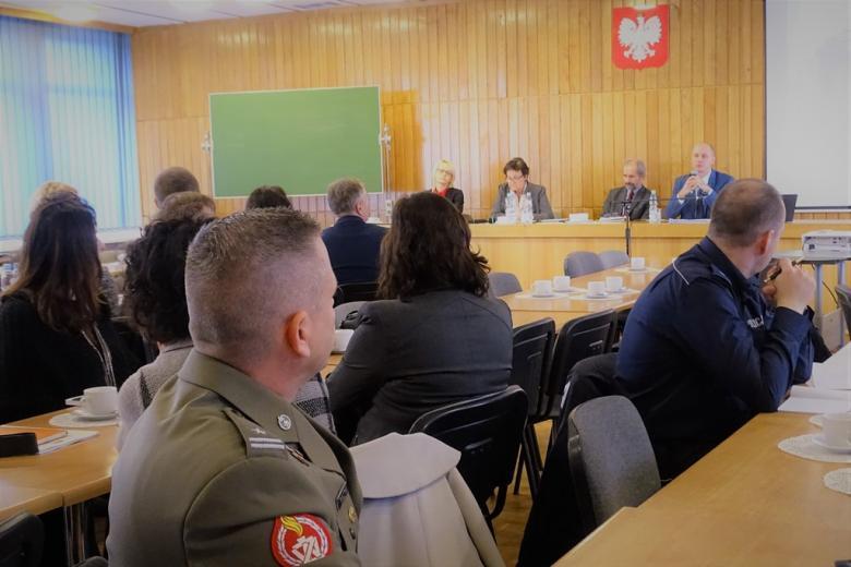 zdjęcie: kilkadziesiat osób siedzi przy stołach, przed nimi dwie kobiety i dwaj mężczyźni siedzą za stołem prezydialnym