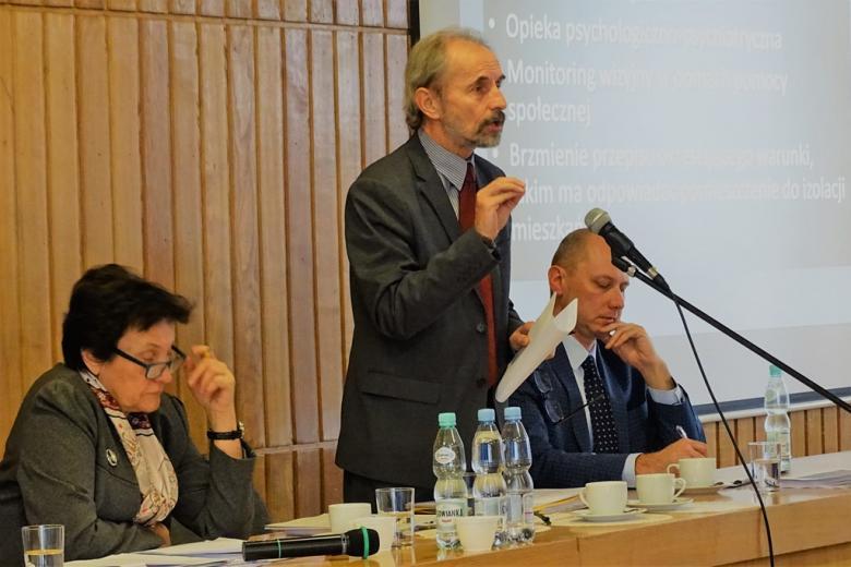 zdjęcie: kobieta i dwaj mężczyźni, jedne z nich stoi i mówi do mikrofonu