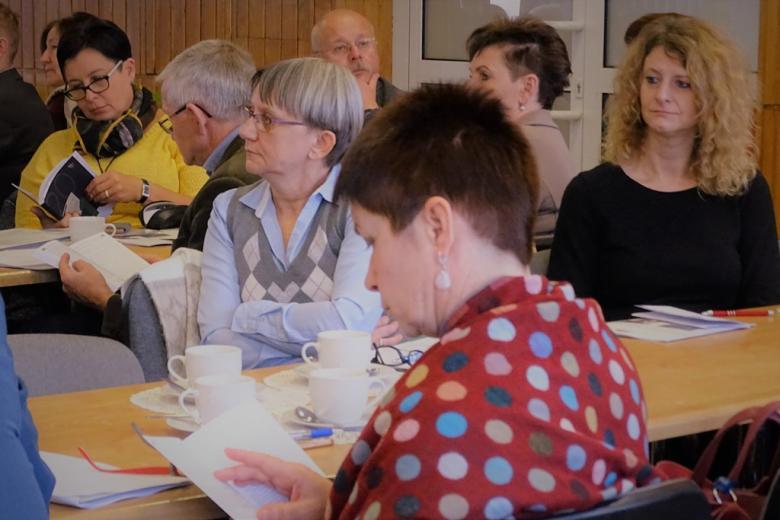 zdjęcie: kilka osób siedzi na sali i przegląda publikacje