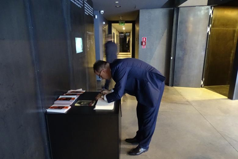 Zdjęcie: pochylony męzczyzna wpisuje się do księgi pamiątkowej w muzeum