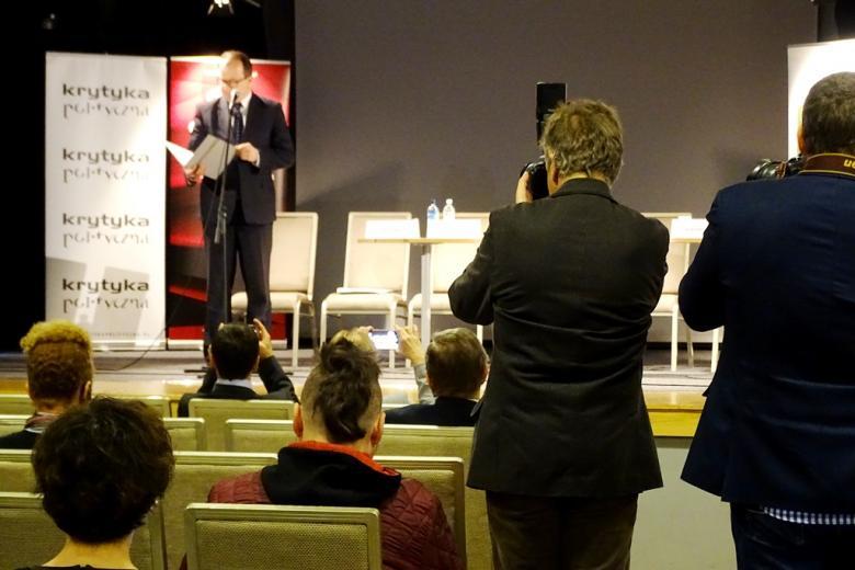 zdjęcie: na scenie stoi mężczyzna w garniturze, przed nim siedzi kilka osób, po prawej stronie stoi dwóch fotografów