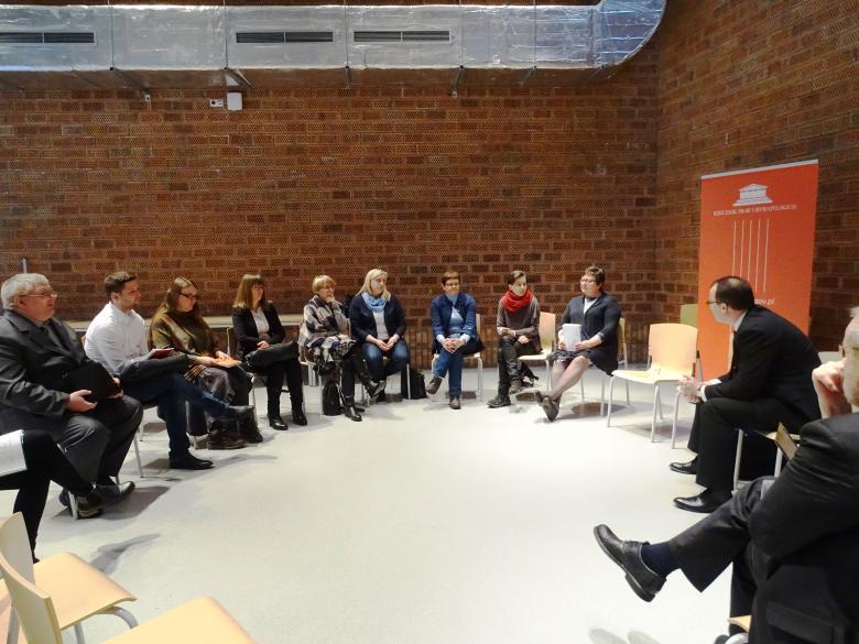 Zdjęcie: spotkanie rzecznika, który siedzi w kręgu razem z uczestnikami. W tle logo RPO