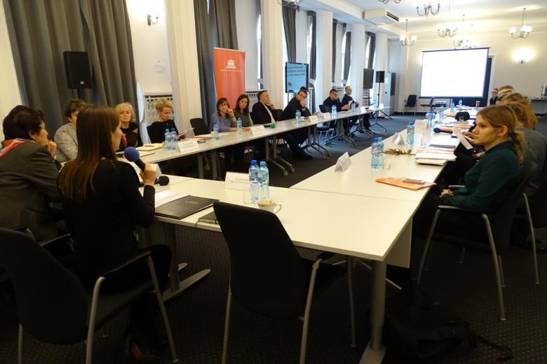 zdjęcie: kilkanaście obiet siedzi przy białych stołach
