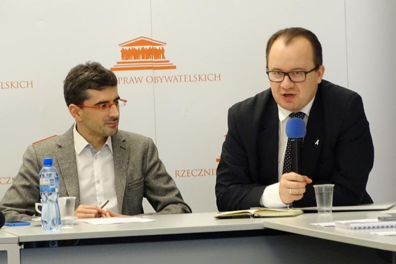 zdjęcie: przy stole siedzi dwóch mężczyzn w okularach, jeden z nich mówi do mikrofonu